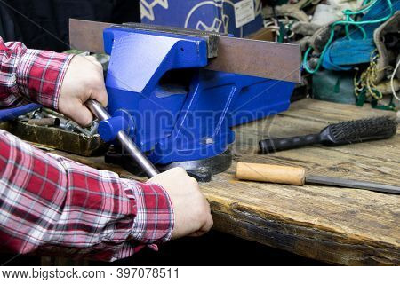 Blue Vise On A Wooden Table. Bench Tools. Vice. Mens Hands Hold A Vise. A Locksmith Vise