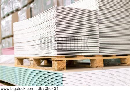 Pallet With Drywall Sheets Plasterboard In The Building Warehouse Store. Stacking Of White Gypsum Pa