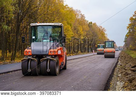 Road Repair, Compactor Lays Asphalt. Heavy Special Machines. Asphalt Paver In Operation. Heavy Vibra