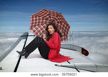 Brunette sat on the wing of an airplane