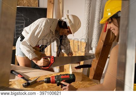 You Will Give Joy To Work On A Construction Site. Two Young Girls, A Blonde And A Brunette, Happily
