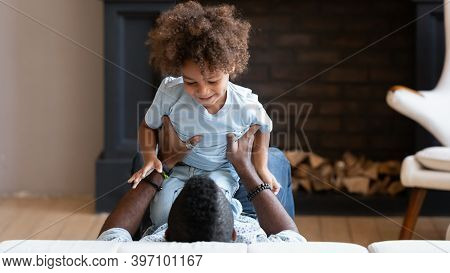 Happy Black Father And Little Son Tickling Giggling On Bed