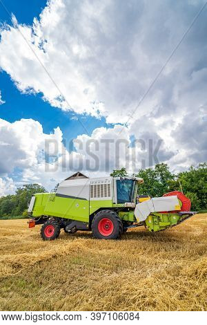 Combine Working On The Large Wheat Field Harvesting Yellow Ripe Wheat. Agricultural Concept. Sunny D