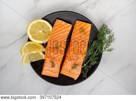 Raw Salmon Filet With Rosemary And Lime On Dark Slate Background, Wild Atlantic Fish. Delicious Fish