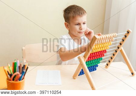 Child Solving Maths Exercises. 7 Years Old Boy Doing Maths Lessons Sitting At Desk In His Room.