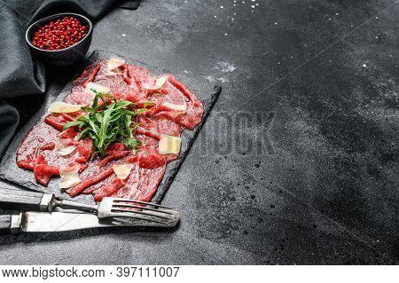 Italian Beef Carpaccio With Arugula Salad, Parmesan Cheese. Black Background. Top View. Copy Space