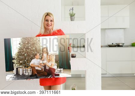 Canvas Prints. A Woman Holding Photo Canvas. Photo Printed On Glossy Synthetic Canvas And Stretched
