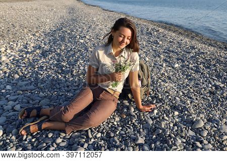 Young Smiling Woman Hiker Sits On Deserted Pebble Beach And Holds Small Bouquet Of Wildflowers. Conc