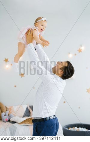 Father Lifting Baby Girl. Happy Father Picks Up And Throws His Lifting A Small Child. Home Atmospher