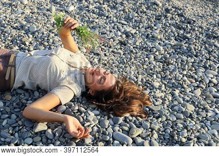 Young Smiling Woman Laying On Pebble And Holds Small Bouquet Of Wildflowers. Concept Of Serenity And
