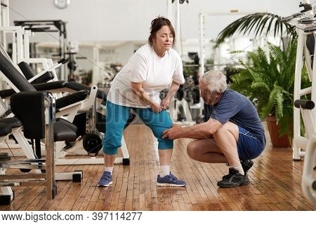 Senior Woman With Severe Muscle Cramps In Her Leg. Man Helping An Injured Woman At Gym.