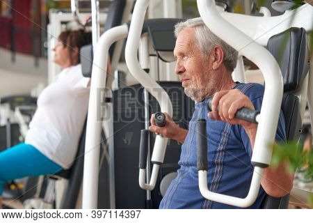 Older Man Doing Strength Exercise At Gym. Mature Man Working Out At Fitness Club. Resistance Exercis