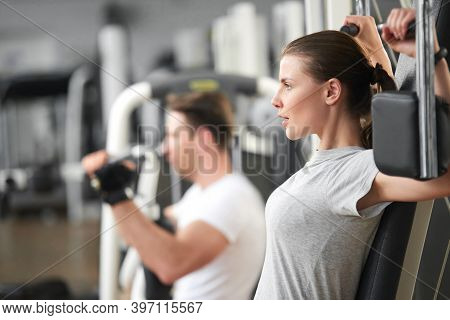 Confident Young Woman Training At Gym. Young Determined Woman At The Sport Gym Doing Arms Exercises