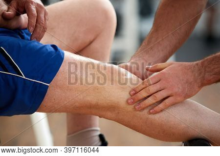 Close Up Man With Injured Leg In Gym. Close Up Of Unrecognizable Man Helping Injured Sportsman At Fi