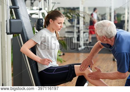 Young Fit Woman Injured Leg During Workout. Male Fitness Instructor Assisting Young Woman Who Had In