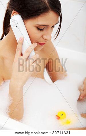 Schöne junge Frau, die reden von Mobiltelefonen während ein Bad zu nehmen