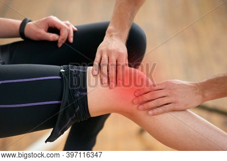 Injured Leg Of Young Woman In Sport Club. Close Up Young Male Hands Examining Injured Female Leg Aft