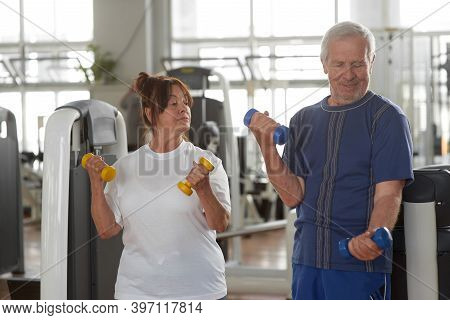 Seniors Lifting Weights At Gym. Elderly Couple Lifting Dumbbells At Fitness Center. Weight Training
