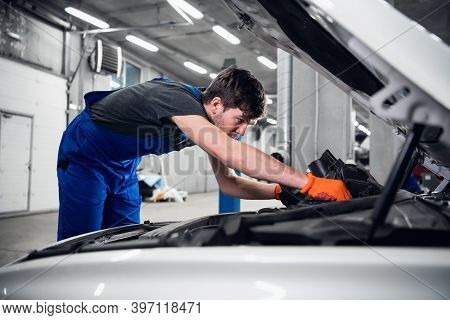 Worker Inspects The Engine Under The Car Hood