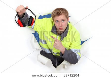young craftsman pointing at earmuffs