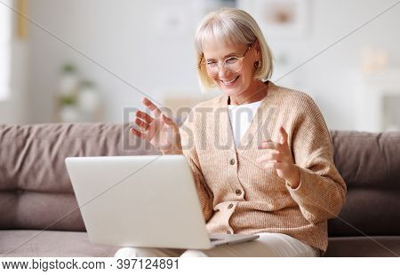 Positive Middle Aged Female With Gray Hair Sitting On Couch At Home And Talking On Video Chat Via Ne
