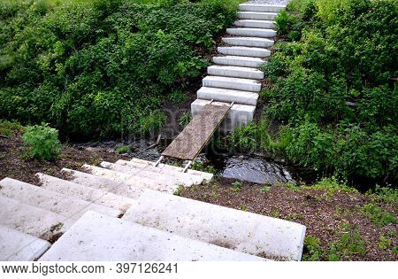 Stairs To The Deep Riverbed On Both Sides Formed By Light Concrete Stairs, Which Are Also Seats. In