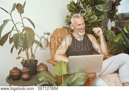 Happy Middle Aged Caucasian Man In Casual Clothes Using Laptop While Sitting On The Balcony Or Terra