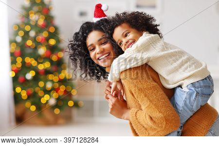 Side View Of Happy Ethnic Woman Giving Piggyback Ride To Boy And Smiling While Having Fun At Home Du