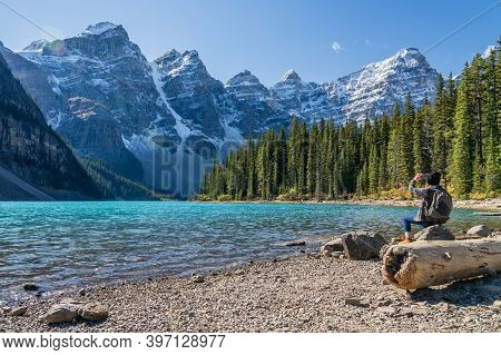 Moraine Lake Rockpile Trail In Summer Sunny Day Morning, Tourists Taking Pictures On The Beautiful S