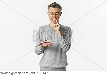 Portrait Of Handsome Middle-aged Man In Glasses And Gray Sweater, Looking Tempted At Delicious Cake,