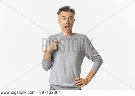 Portrait Of Handsome Middle-aged Gay Man Looking Surprised, Pointing At Himself, Being Chosen, Stand