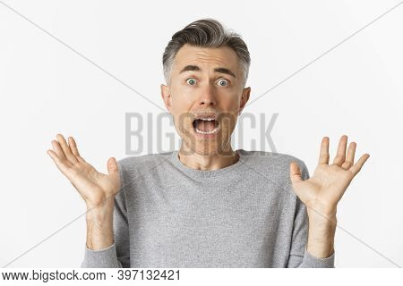 Close-up Of Scared Middle-aged Man, Looking Startled, Jumping And Screaming Frightened, Standing Amb