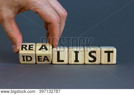 Idealist Or Realist. Male Hand Flips Wooden Cubes And Changes The Word 'idealist' To 'realist' Or Vi