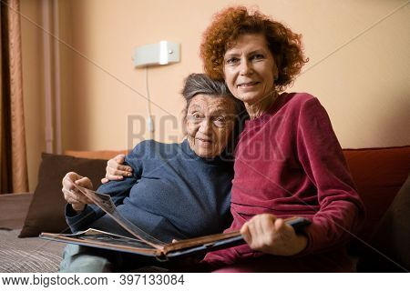 Senior Woman And Her Adult Daughter Looking At Photo Album Together On Couch In Living Room, Talking