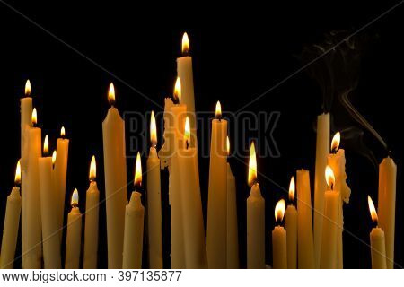 Row of white burning church candles against a black background