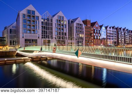 Footbridge Over The Motlawa River And Modern Architecture Of Granaries Island In Gdansk At Night. Po