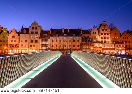 Footbridge Over The Motlawa River And Beautiful Architecture Of Gdansk Old Town At Night. Poland