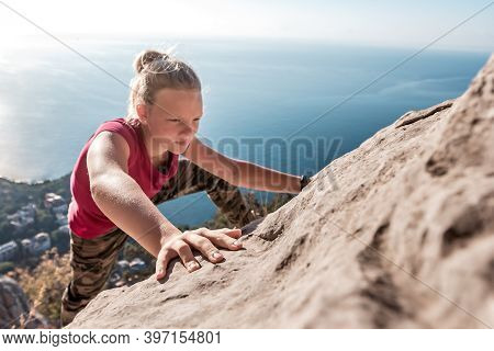 Purposeful Young Girl Climbs To Top Of Mountain. Courage And Concentration. Fingers Clinging To Rock