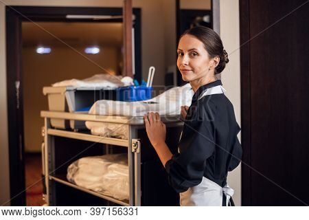 Smiling Hotel Maid With Fresh Towels Doing Housekeeping.