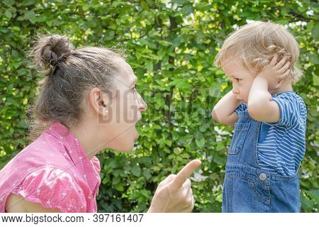 Angry Mother Shout At Her Naughty Son In The Park While The Little Child Cover His Ears Avoiding Mad