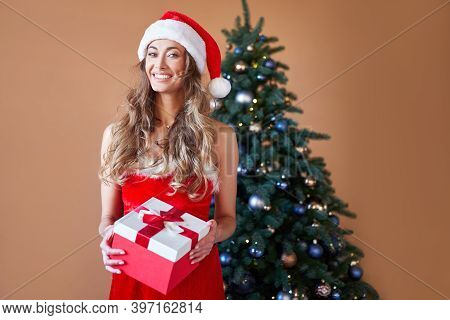 Christmas Woman Red Dress Costume Santa Hat Standing Near Christmas Tree. Caucasian Female Middle Ag