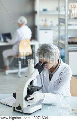Vertical Portrait Of Young Female Scientist Looking In Microscope While Studying Plant Samples In Bi
