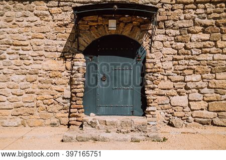 Ancient Stonewall With Black Door. Antique Building Exterior Of Fortes