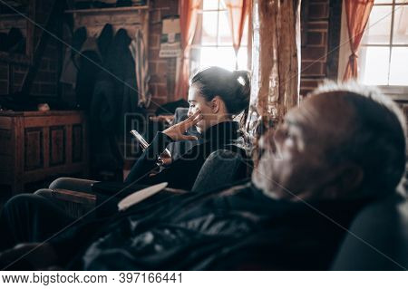 Elderly Man Watching Tv With His Granddaughter By His Side Looking At Her Phone
