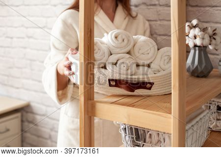 Young Woman In Warm Robe Is Organizing Linen Closet With Neatly Folded Towels, Sheets And Blankets.