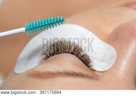 Close Woman Eye with Eyelashes Extension with eyepatch under eye and brush for care after beauty treatment closeup stock photo