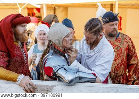 Russia. Vyborg. 08.20.2020 A Girl In A Knights Costume Is Helped To Put On A Helmet