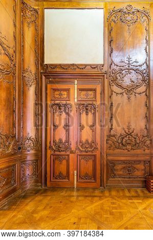 Front View Of Closed Elegant Lumber Door With Engraved Decorations, Installed In Wooden Ornamental A
