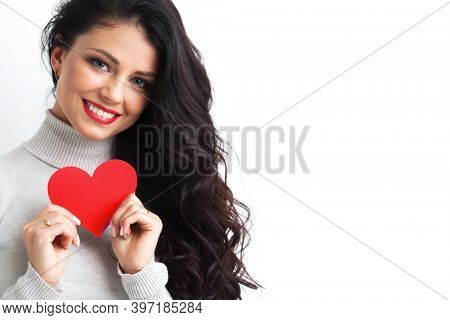 Pretty caucasian woman with toothy smile holding Valentines Day red heart shape paper card in hands, white background with copy space