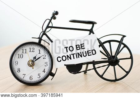 Card With Text To Be Continued. On The Table There Is A Clock In The Shape Of A Bicycle With A Card.
